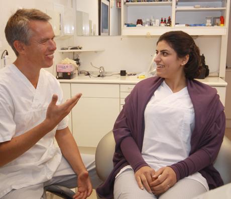 Erik Svendsrud snakker med en pasient i tannlegestolen